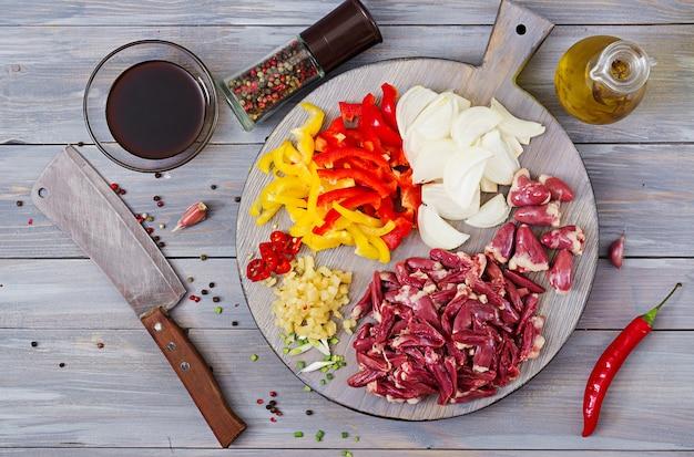 Ingrediënten voor het roerbakken van kippenharten, paprika en uien. chinese keuken