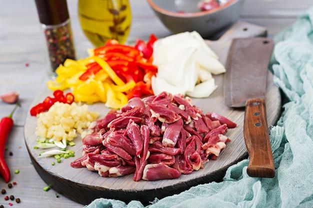 Ingrediënten voor het roerbakken van kippenharten, paprika en uien.