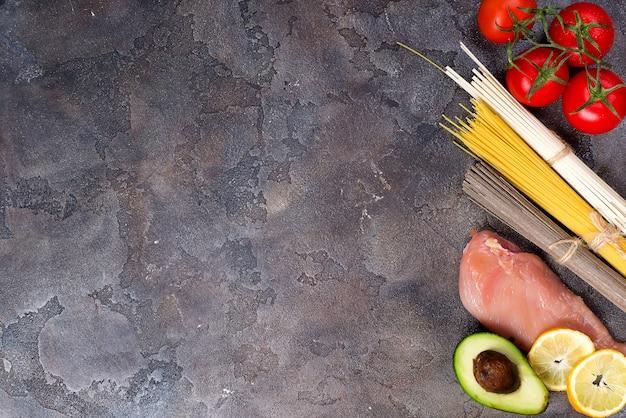 Ingrediënten voor het voorbereiden van pasta of aziatische noedels met tomaat en vlees op stenen achtergrond.