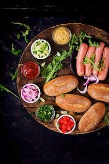 Ingrediënten voor hotdog met komkommer, tomaat en rode ui op houten oppervlak. bovenaanzicht plat leggen