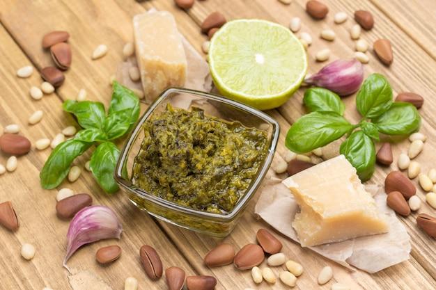 Ingrediënten voor huisgemaakte pesto: basilicumblaadjes, parmezaan, pijnboompitten, knoflook, halve citroen. bovenaanzicht. lichte houten achtergrond. detailopname