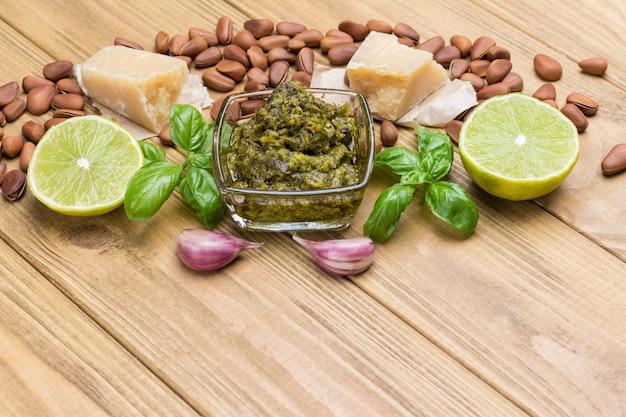 Ingrediënten voor huisgemaakte pesto: basilicumblaadjes, parmezaan, pijnboompitten, knoflook, halve citroen. bovenaanzicht. lichte houten achtergrond. kopieer ruimte