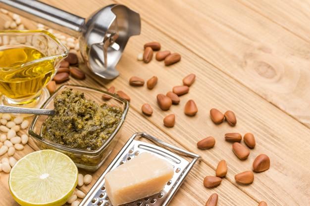 Ingrediënten voor huisgemaakte pesto. parmezaanse kaas op rasp, pestosaus in glazen beker.