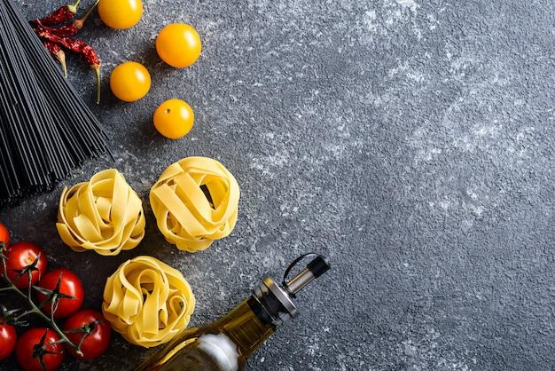 Ingrediënten voor italiaans diner van pasta, zwarte spaghetti, fettuccine, tomaten, olijfolie, chilipepers op grijze achtergrond met kopie ruimte