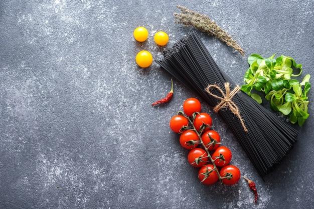 Ingrediënten voor italiaans diner - zwarte spaghetti met inktvisinkt, groenten op grijze achtergrond met exemplaarruimte, vegetarisch voedselconcept