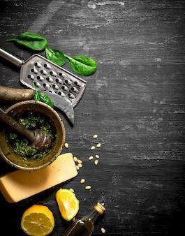 Ingrediënten voor italiaanse pesto op de zwarte houten tafel.