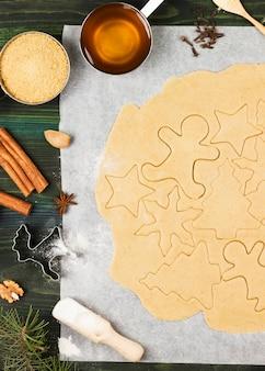Ingrediënten voor kerstmis-gemberpeperkoeken met honing en kaneel op hout