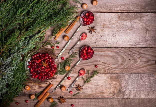 Ingrediënten voor kerstmis, winterkoekjes bakken. peperkoek, fruitcake, seizoensgebonden drankjes. veenbessen, gedroogde sinaasappelen, kaneel, kruiden op een houten tafel, kopie ruimte bovenaanzicht.