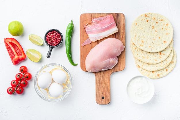 Ingrediënten voor kippentaco's, tomaten, maïs, ei, paprika, limoenkippenvlees en tortilla's over wit