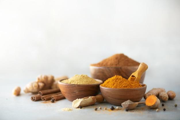 Ingrediënten voor kurkuma latte. gemalen kurkuma, kurkuma wortel, kaneel, gember, zwarte peper op grijze achtergrond.