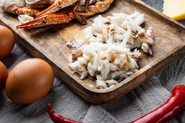 Ingrediënten voor ontbijtomelet met krabvlees en kaasreeks, op grijze lijst