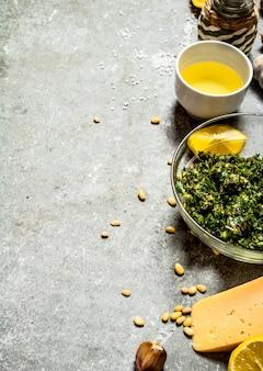 Ingrediënten voor pesto op de stenen tafel.