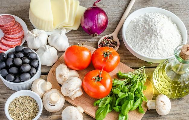 Ingrediënten voor pizza op de houten achtergrond
