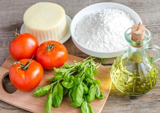 Ingrediënten voor pizza op hout