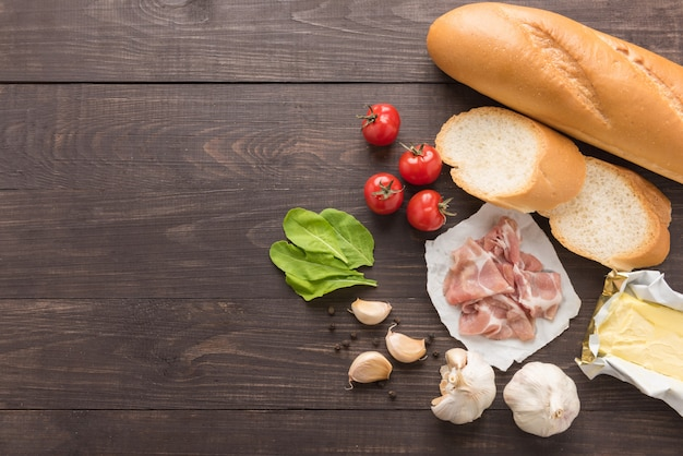 Ingrediënten voor sandwich met gerookt vlees, stokbrood op houten tafel
