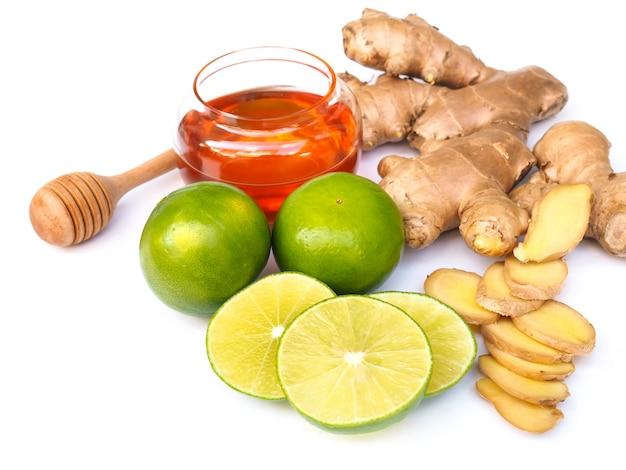 Ingrediënten voor sapdranken van thee met honing, limoen, citroen, citrus en gember die op witte ruimte wordt geïsoleerd.