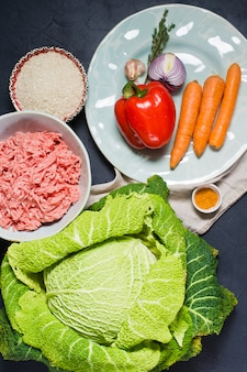 Ingrediënten voor savooikool gevuld met vlees en groenten. wortelen, paprika, uien, knoflook, tijm, kruiden, rijst
