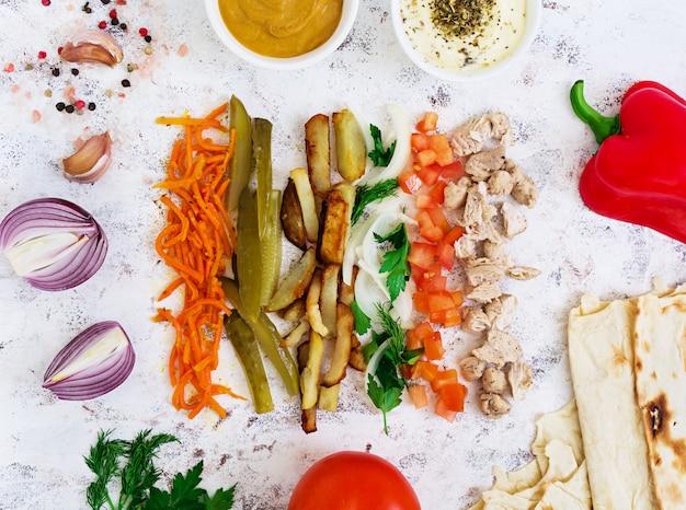 Ingrediënten voor shoarmasandwich op wit