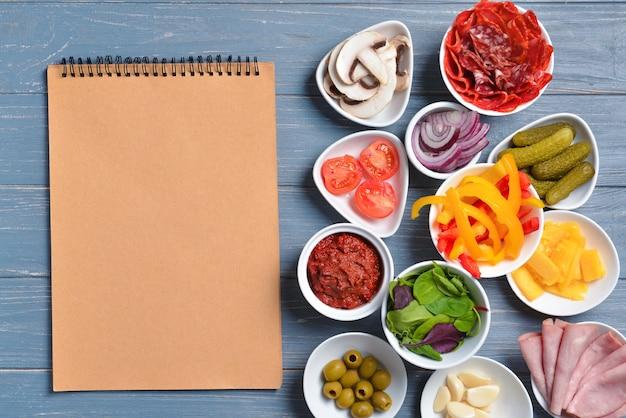 Ingrediënten voor smakelijke pizza en notitieboekje op houten achtergrond