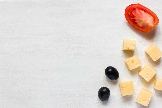 Ingrediënten voor snacks, kaas met olijven en tomaat op een witte tafel