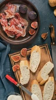 Ingrediënten voor spaanse tapas, pinchos of bruschetta voorgerechten. lekkere ham, jamon, stokbrood, vijgen, kaas en kruiden op de eettafel.