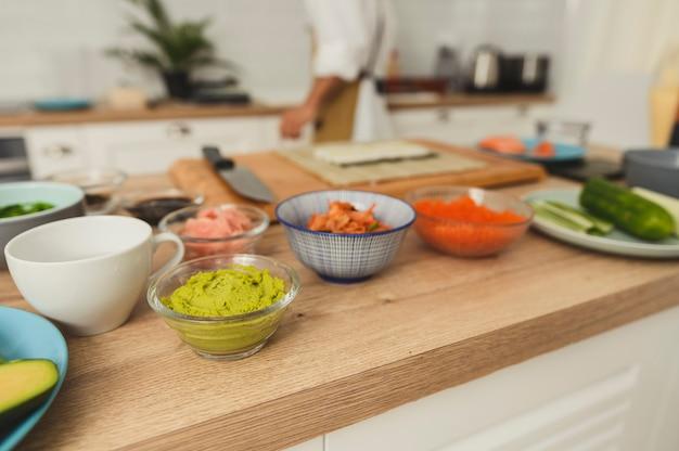 Ingrediënten voor sushi en broodjes op een keukentafel rijst rood ingelegde gember komkommer krabvlees zalm