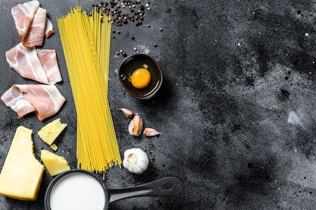Ingrediënten voor traditionele italiaanse pasta alla carbonara. ongekookte spaghetti, pancetta-spek, parmezaanse kaas, ei. bovenaanzicht. kopieer ruimte