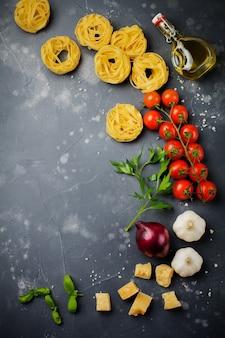 Ingrediënten voor traditionele italiaanse pastagerecht. ongekookte rauwe tagliatelle bolognesi, parmezaanse kaas, olijfolie, knoflook, basilicumblaadjes, paprika, kerstomaatjes. bovenaanzicht