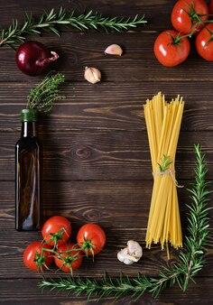 Ingrediënten voor vegetarisch spaghettirecept. volkoren pasta op een rustieke donkere houten tafel