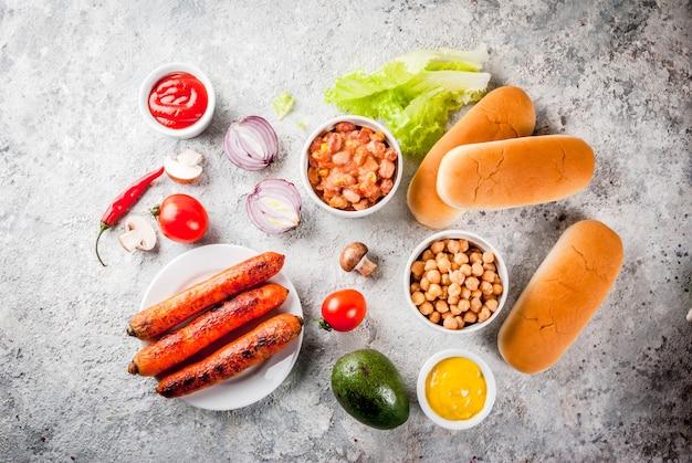 Ingrediënten voor verschillende zelfgemaakte vegan wortel hotdogs, met gebakken ui, avocado, chili, champignons, tomaten en bonen, grijze steen copyspace bovenaanzicht