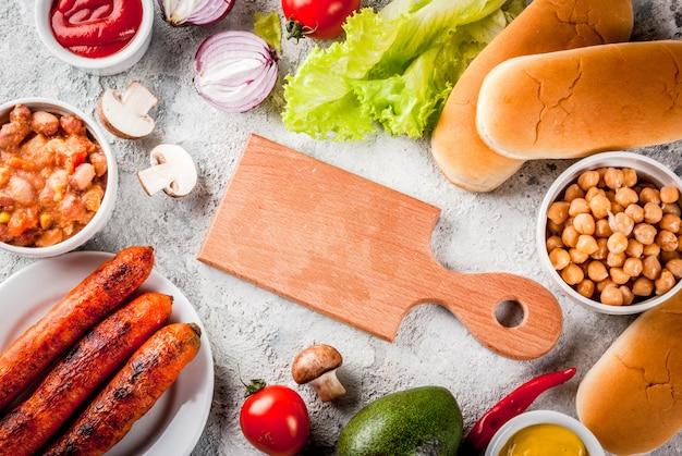 Ingrediënten voor verschillende zelfgemaakte vegan wortel hotdogs met gebakken ui avocado chili champignons tomaten en bonen grijze stenen achtergrond