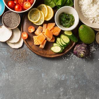 Ingrediënten voor voorbereiding por kom met zalm, avocado, groenten en chia zaden bovenaanzicht