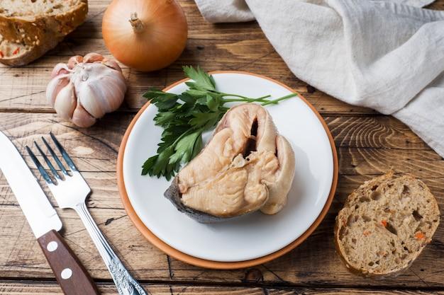 Ingrediënten voor zalm vissoep, stukjes brood, ui en knoflook met greens op houten achtergrond.