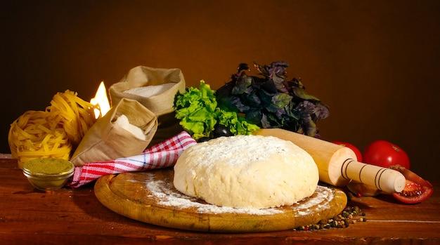 Ingrediënten voor zelfgemaakte pizza op houten tafel op bruine achtergrond