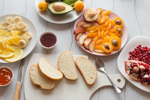 Ingrediënten voor zoete toast sneetjes brood en diverse vruchten abrikozen, granaatappels, perziken, avocado's, sinaasappels, bananen op een witte houten tafelblad bekijken