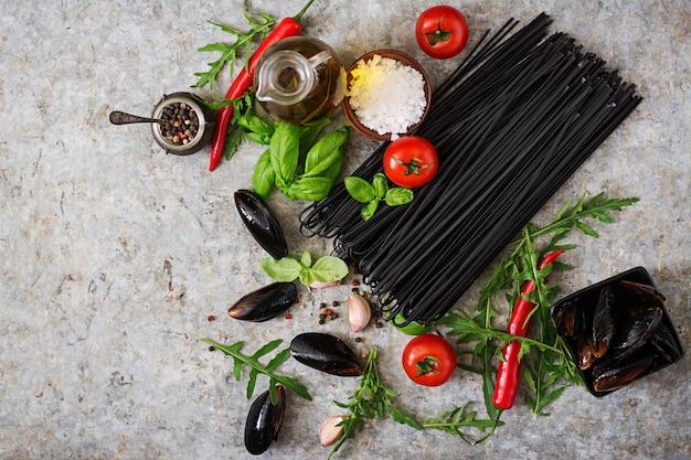 Ingrediënten voor zwarte linguine-pasta - tomaat, basilicum, chilipepers en mosselen. bovenaanzicht