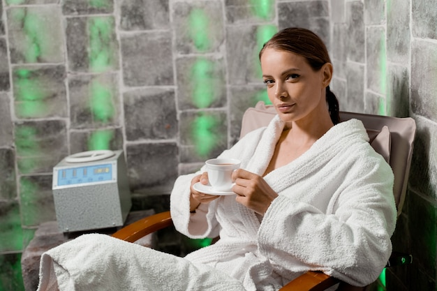 Inhalatietherapie in de zoutkamer in de spa. jonge vrouw met kopje thee ontspannen.
