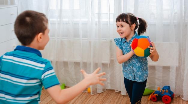 Inheemse kinderen, een jongen en een meisje, spelen in een speelkamer voor kinderen en gooien een bal