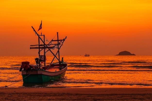 Inheemse vissersboot in thaise stijl verankerd op het strand in het ochtendlicht met eiland en kleurrijke lucht op de achtergrond.