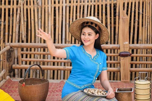 Inheemse vrouw in het noordoosten van thailand in blauwe jurk en technologie