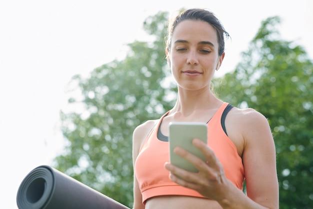 Inhoud aantrekkelijk meisje in sportbeha oefeningsmat houden en het bekijken van yoga-oefening op telefoon buitenshuis