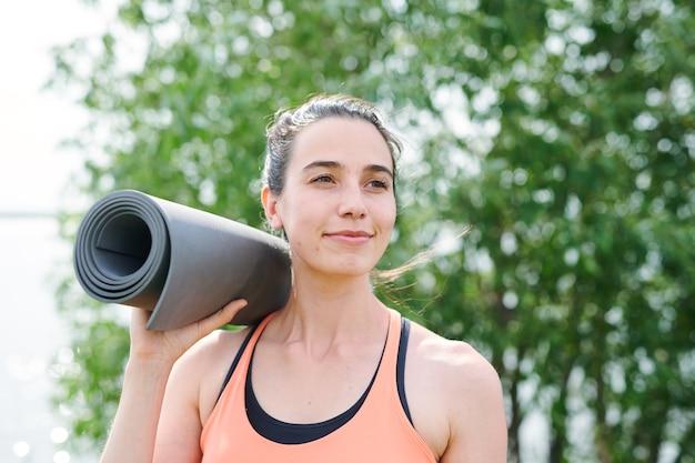 Inhoud doelgerichte yoga trainer oefeningsmat op schouder houden en buitenshuis op zoek naar afstand