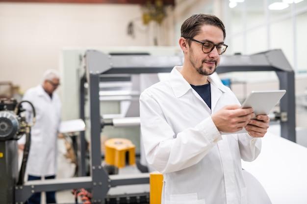 Inhoud jonge bebaarde specialist in glazen met behulp van digitale tablet tijdens het analyseren van afdrukbronnen in de fabriek