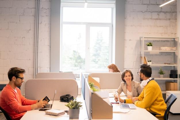 Inhoud jonge collega's bespreken projectdoelen terwijl jonge man in oranje trui identiteitsbewijs controleert