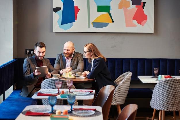 Inhoud jonge zakenmensen kijken naar online presentatie op tablet tijdens zakelijke bijeenkomst in trendy café