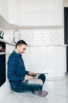 Inhoud knappe jonge bebaarde freelancer zittend op de vloer en camera kijken tijdens het werken buitenshuis, hij met behulp van moderne laptop in de keuken
