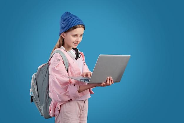 Inhoud moderne tienermeisje met schooltas surfen op internet op laptop