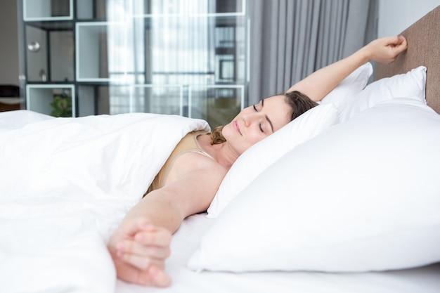 Inhoud mooie vrouw wakker in bed