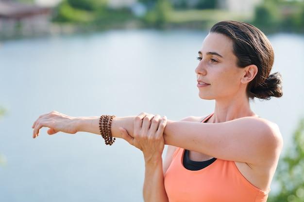 Inhoud peinzende jonge vrouw arm naar de borst duwen tijdens het strekken van biceps buitenshuis