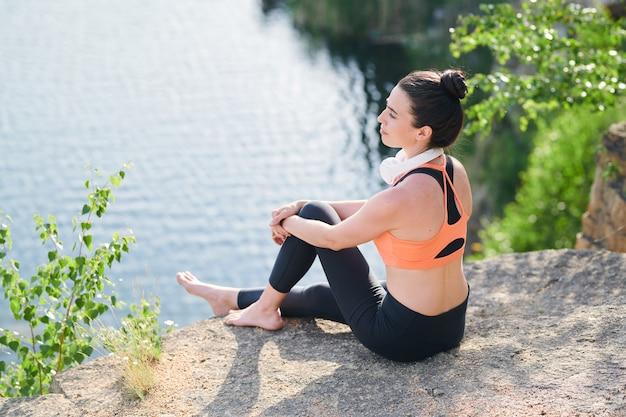Inhoud rustige jonge vrouw in sportkleding zittend op de rand van de steengroeve en de natuur overweegt terwijl hij rust na een buitentraining